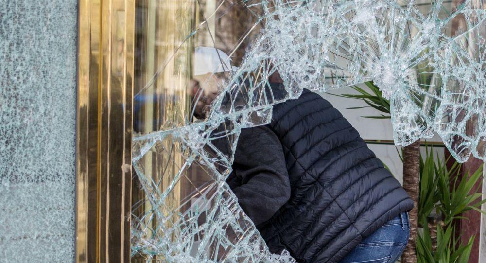 Parigi, proteste di piazza: un manifestante entra dentro un negozio dopo aver infranto la vetrina