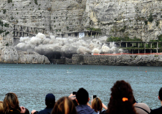 People watch as the cement structure of a 50-year-old illegally built hotel is blown up, on the Sorrento coast, southern Italy, Sunday, Nov. 30, 2014