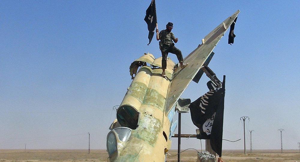 Combattenti dello Stato Islamico sventolano la loro bandiera su un velivolo nemico alla base di Tabqa, a Raqqa, Syria.