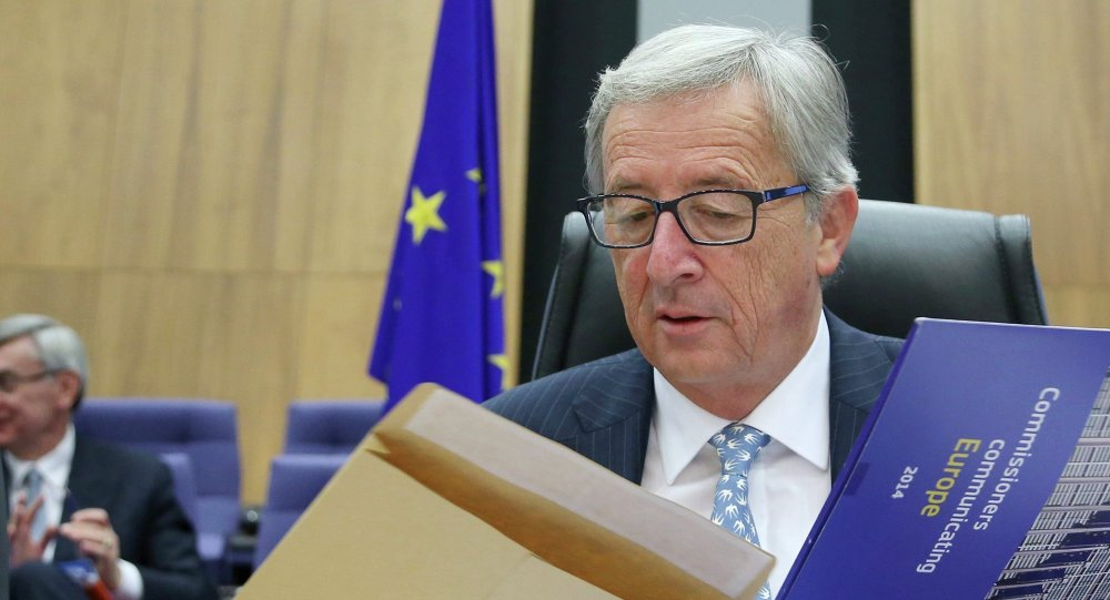 The European Commission's new President Jean-Claude Juncker opens an envelope as he chairs the first official meeting of the EU's executive body at the EU Commission headquarters in Brussels November 5, 2014