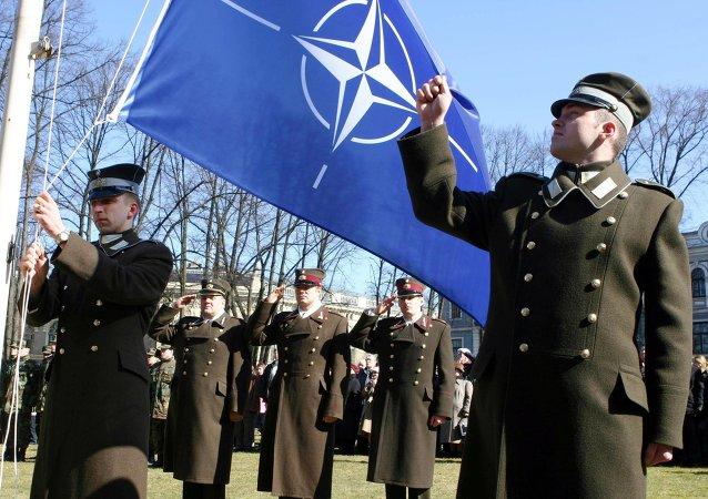 Militari lettoni e la bandiera della Nato