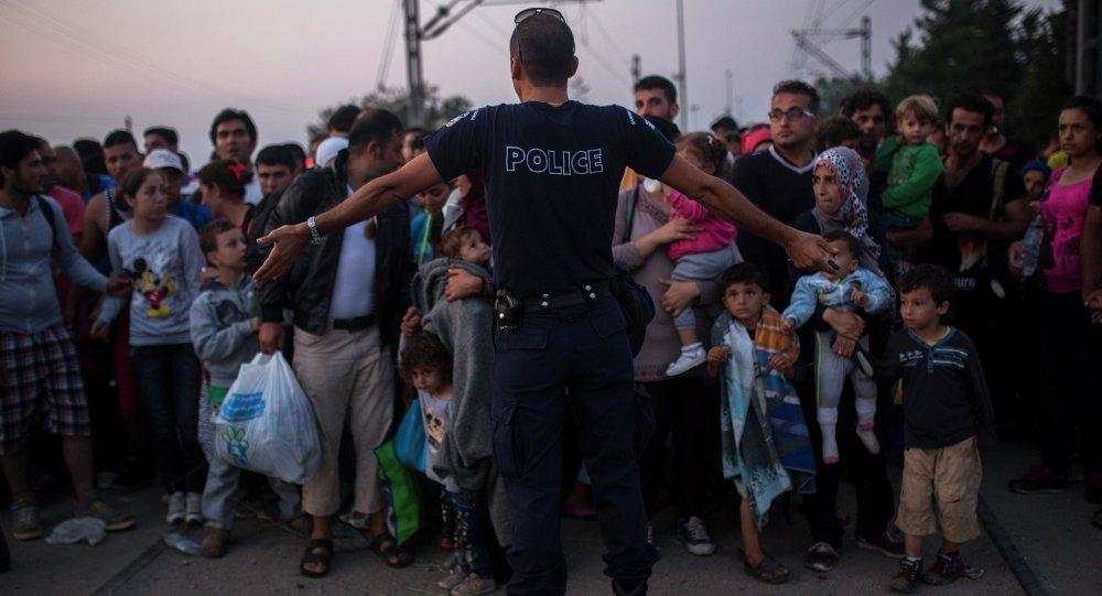 Poliziotto tra migranti in Grecia al confine con la Macedonia