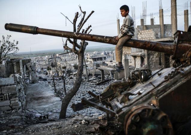 Un ragazzo kurdo sul carro armato destrutto nella città di Kobani, Siria