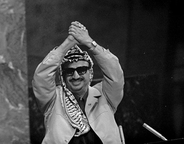13 novembre 1974, Yasser Arafat alza e intreccia le mani in segno di vittoria dopo essere intervenuto alla 70° assemblea dell'ONU