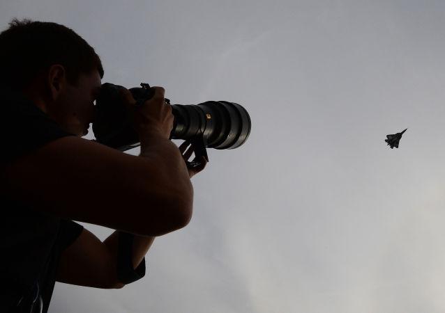 Un fotografo scruta il cielo col suo obiettivo alla ricerca di un caccia russo