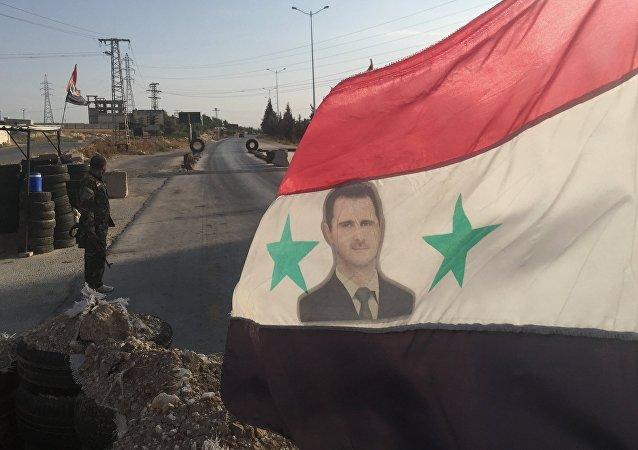 Bandiera siriana con foto di Assad