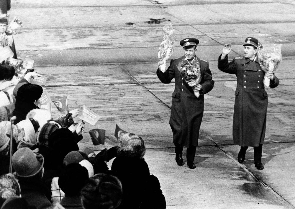 I cosmonauti Aleksey Leonov e Pavel Belyaev salutano la gente che li attende all'aeroporto di Mosca.