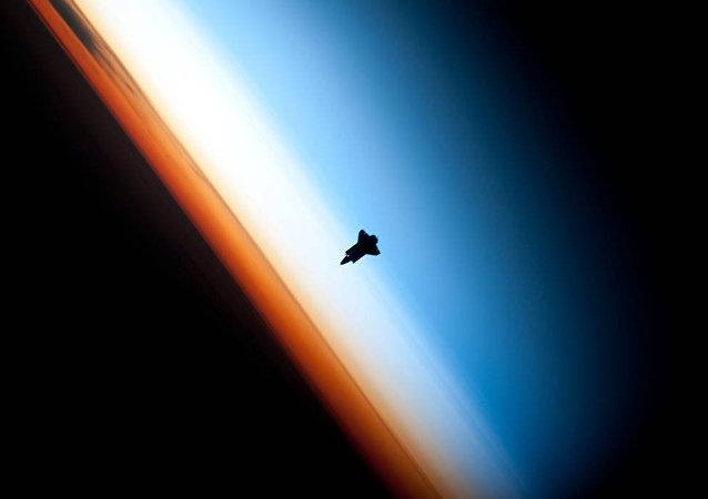 Lo space shuttle Endeavour in volo sull'orizzonte terrestre nel corso del lancio della missione STS-130 del 2010