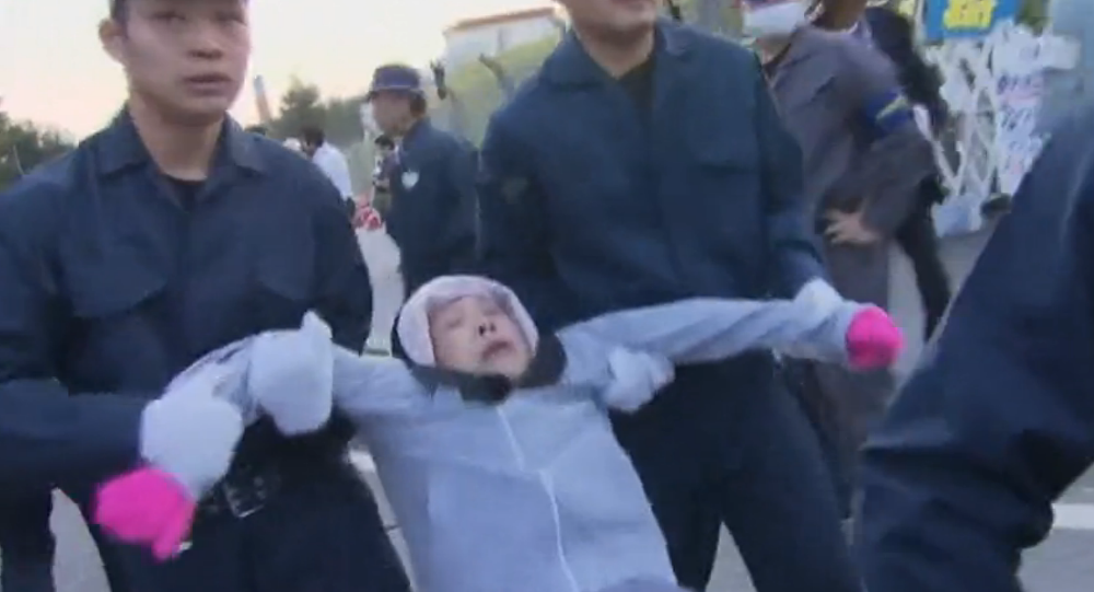 Manifestante portato via dalla polizia ad Okinawa