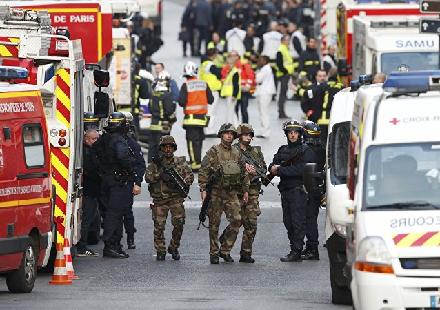 French riot police (CRS), soldiers, firefighters, French red cross members and staff of the emergency medical services in France (SAMU) stand at the scene in Saint-Denis, France, near Paris, November 18, 2015