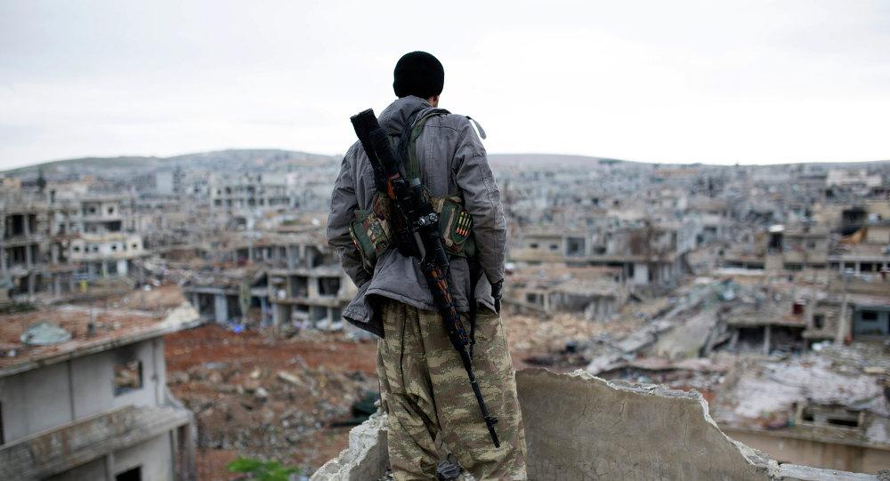 Un combattente straniero sulle macerie di Homs in Siria