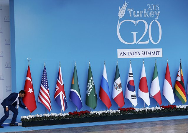 An official adjusts a Turkish national flag prior to the start of the G20 summit in Belek in the Mediterranean resort city of Antalya, Turkey, November 14, 2015
