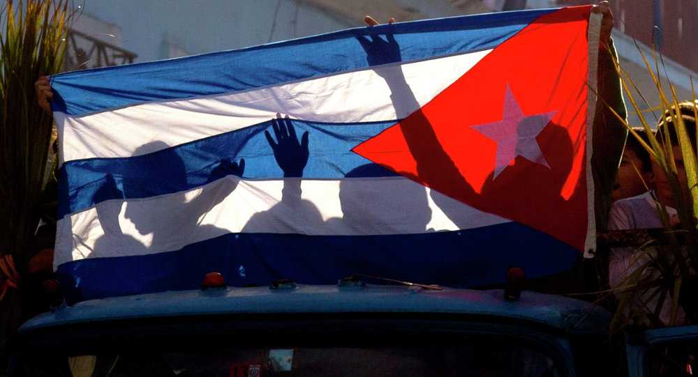 Children's shadows are cast on a Cuban national flag as they take part in a caravan tribute marking the 56th anniversary of the original street party that greeted a triumphant Castro and his rebel army, in Regla, Cuba, Thursday, Jan. 8, 2015