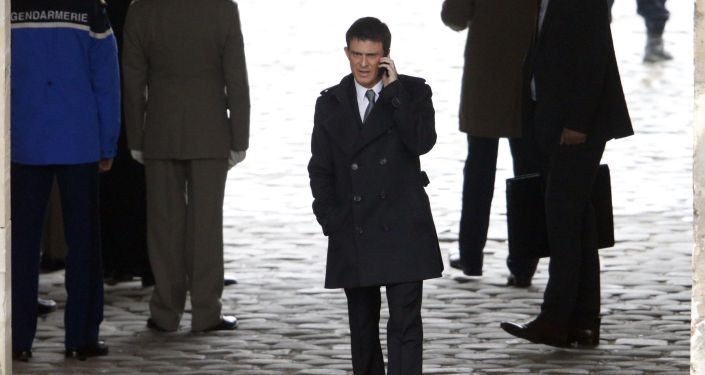 French Prime Minister Manuel Valls talks on his mobile phone before a military ceremony in the courtyard of the Invalides in Paris March 24, 2015.