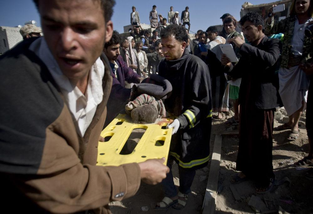 Uomini portano via il cadavere di un bambino dalle macerie di una casa.