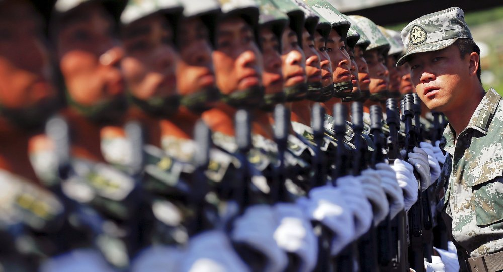 An officer gives instructions as soldiers of China's People's Liberation Army form a line during a training session for a military parade to mark the 70th anniversary of the end of World War Two, at a military base in Beijing, China, August 22, 2015