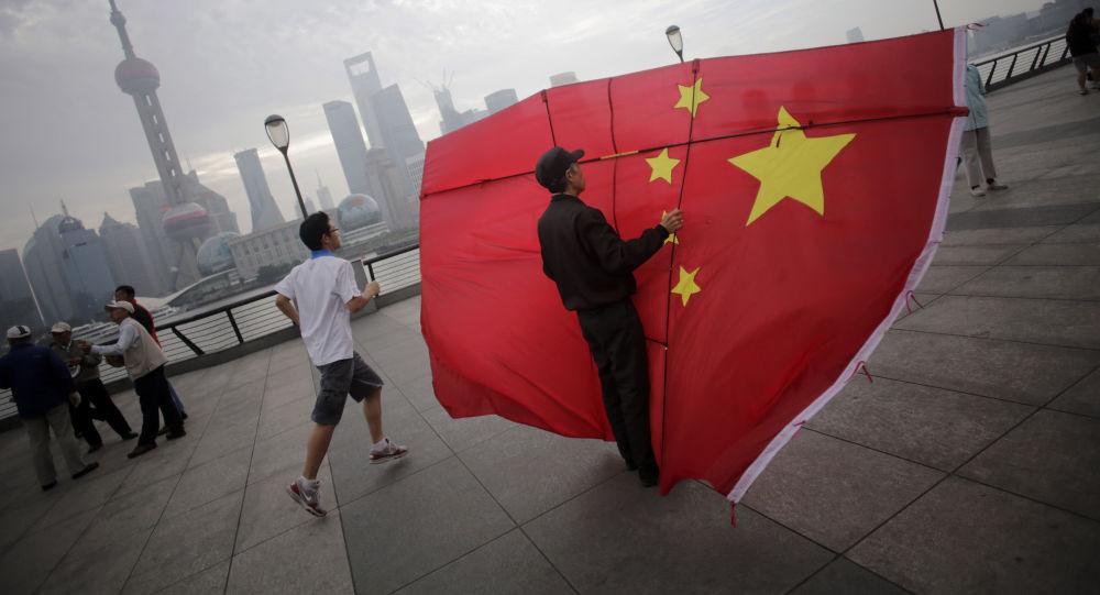 Shangai, un uomo regge una bandiera cinese