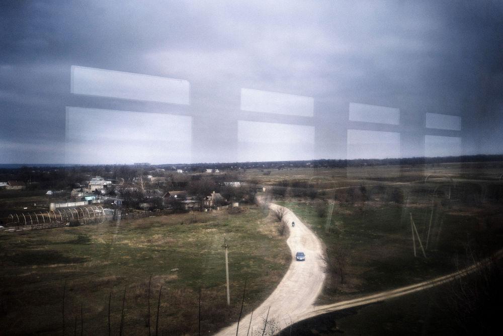 Fuori dal treno scorre la vita nel Donbass ferito dalla guerra.