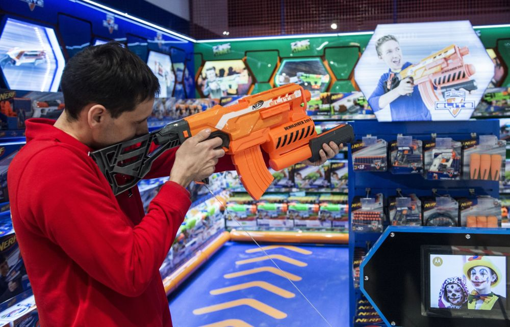 Un commesso prova un fucile giocattolo.