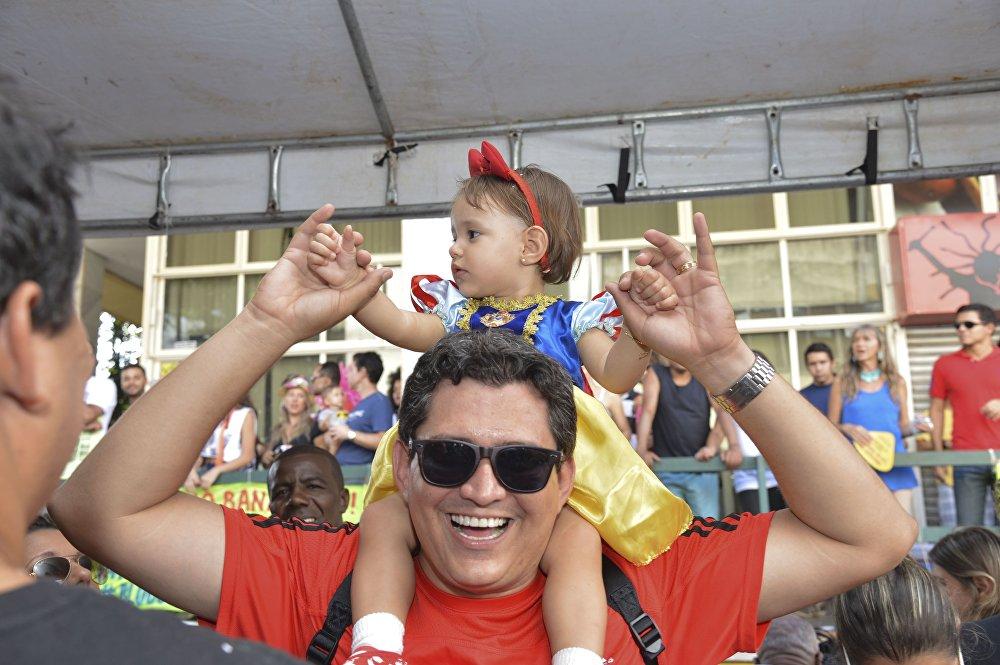 Un papà con sua figlia in braccio ad una sfilata preparatoria del carnevale di Rio.