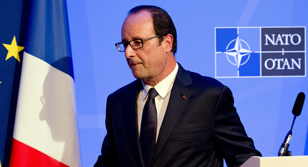 A shadow of France's President Francois Hollande is cast on a flag as he leaves a press conference on the second day of the NATO 2014 Summit at the Celtic Manor Resort in Newport, South Wales, on September 5, 2014