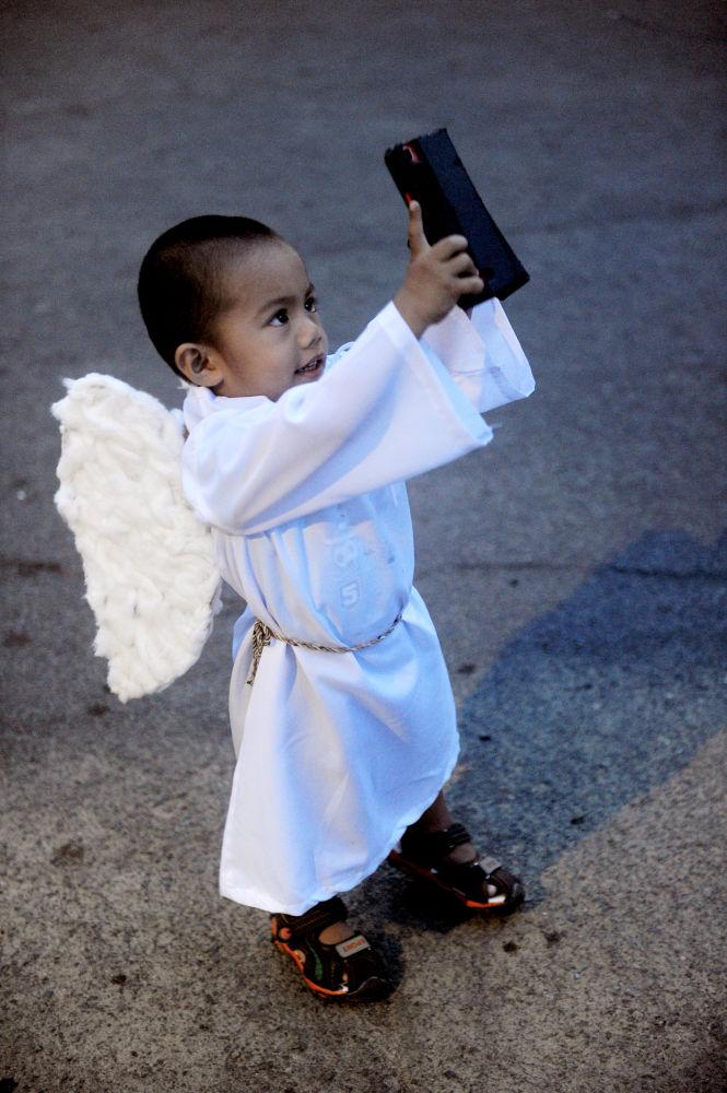 Un bambino vestito da angioletto nelle Filippine.