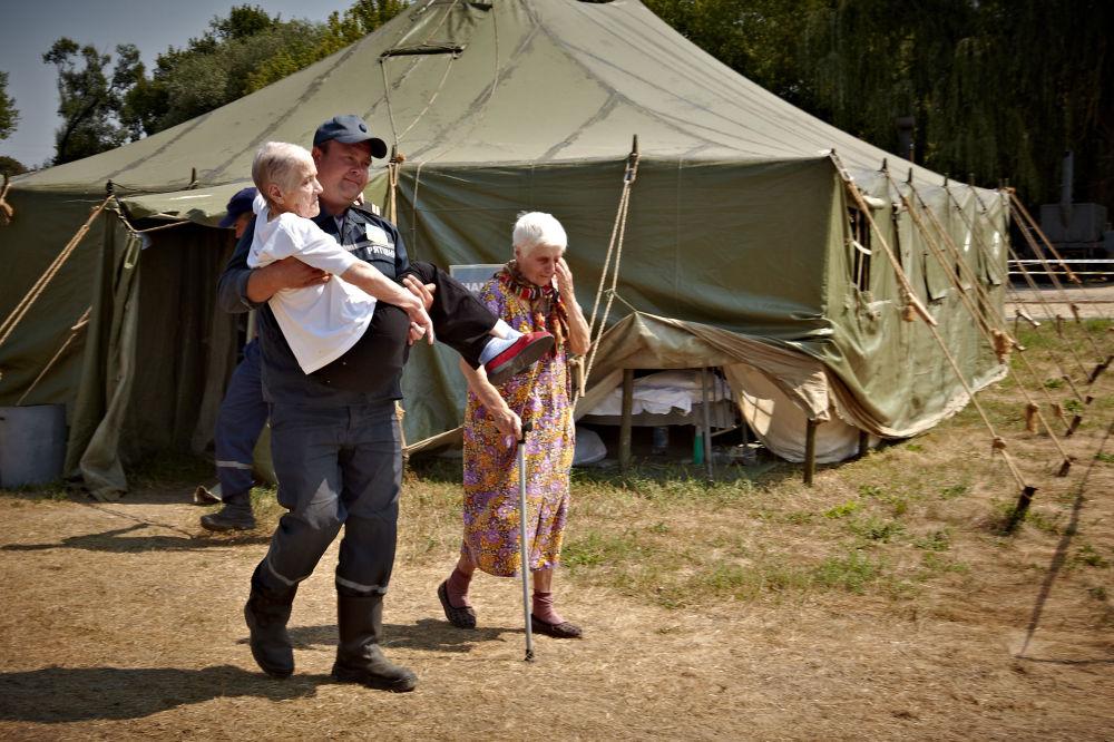 Un operatore della protezione civile ucraina trasporta in braccio una signora anziana in un campo profughi vicino a Lugansk.