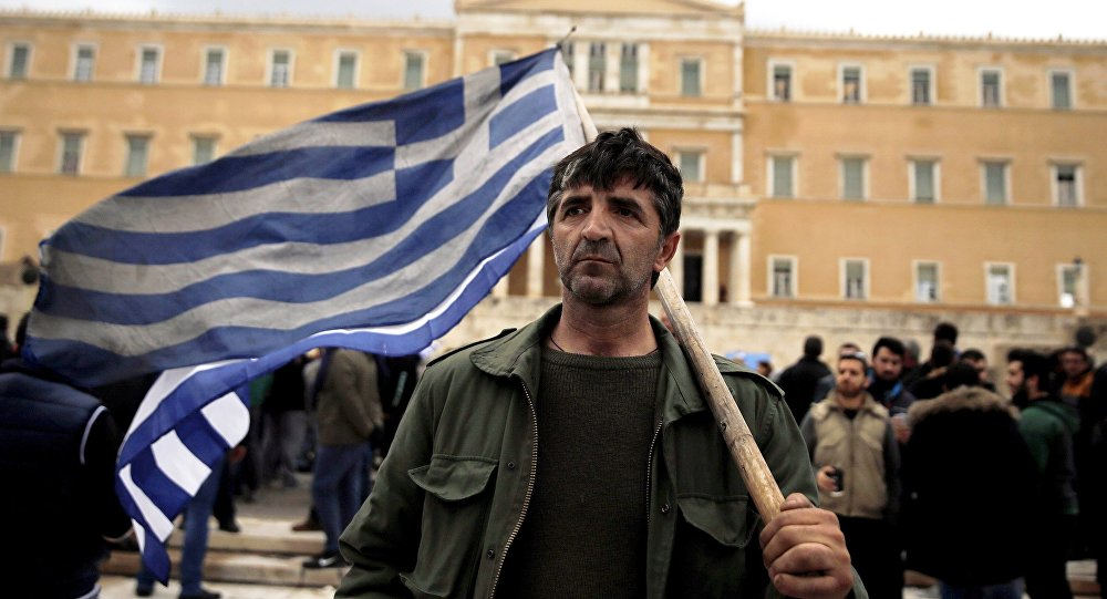 Un agricoltore greco tiene la bandiera greca di fronte al parlamento durante le proteste contro le riforme delle pensioni, il 12 febbraio, 2016