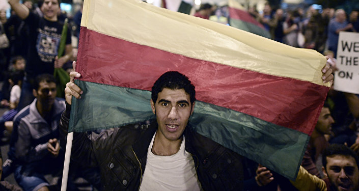 A man holds the flag of the Syrian Kurdish Democratic Union Party (PYD)