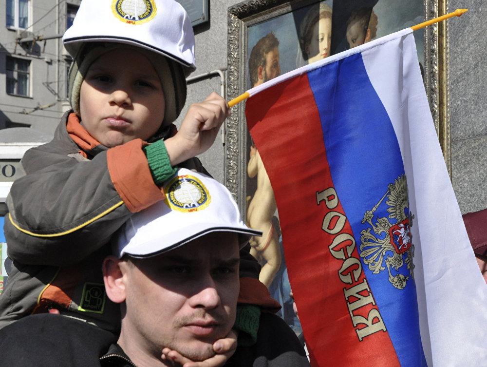 In braccio al papà, con la bandiera russa