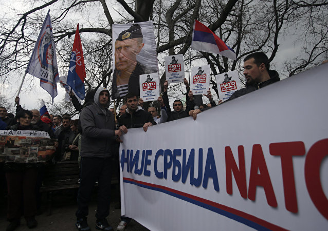 Protesters holding a banner that reads: Serbia is not NATO during a protest against NATO in downtown Belgrade, Serbia, Saturday, Feb. 20, 2016