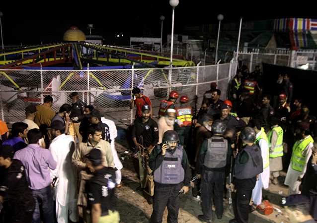 Pakistani police officers and rescue workers gather at the site of bomb explosion in a park in Lahore, Pakistan