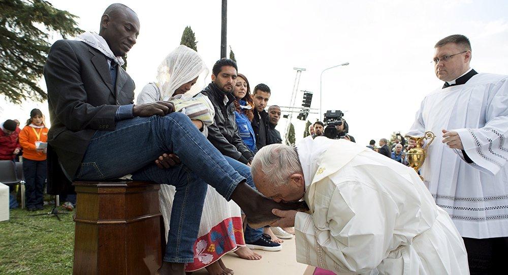 Papa Francesco bacia un piede a un profugo durante il rituale della lavanda dei piedi