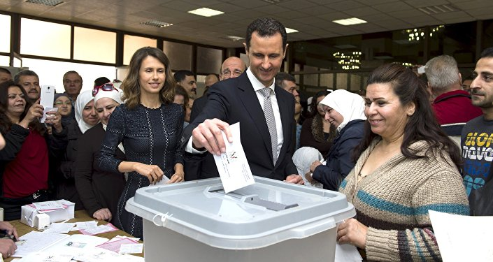 Syria's President Bashar al-Assad (C) casts his vote next to his wife Asma (centre left) inside a polling station during parliamentary elections in Damascus, Syria