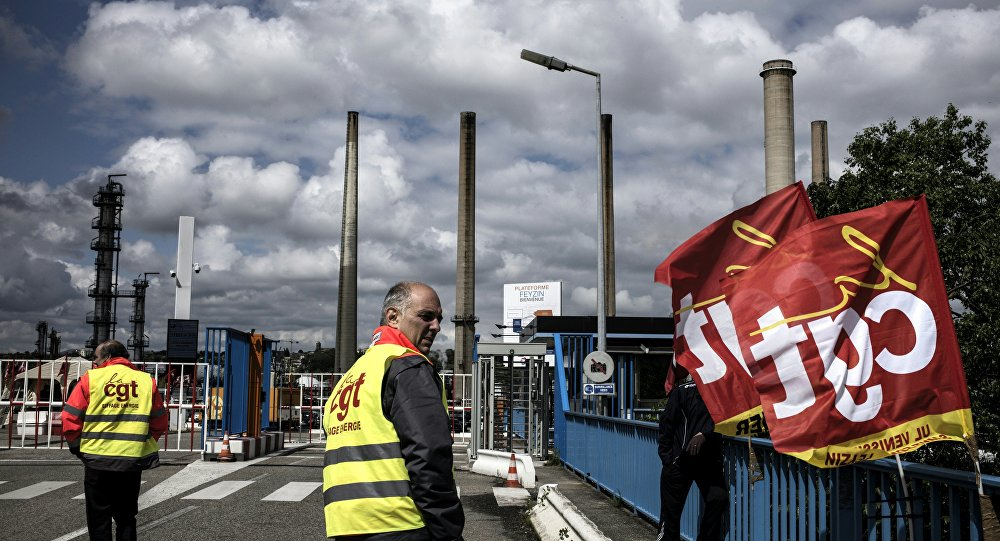 A worker stands next to French CGT union flags in front of the Total oil refinery of Feyzin, near Lyon, central-eastern France, on May 24, 2016, during a strike at the plant to protest against government labour reforms