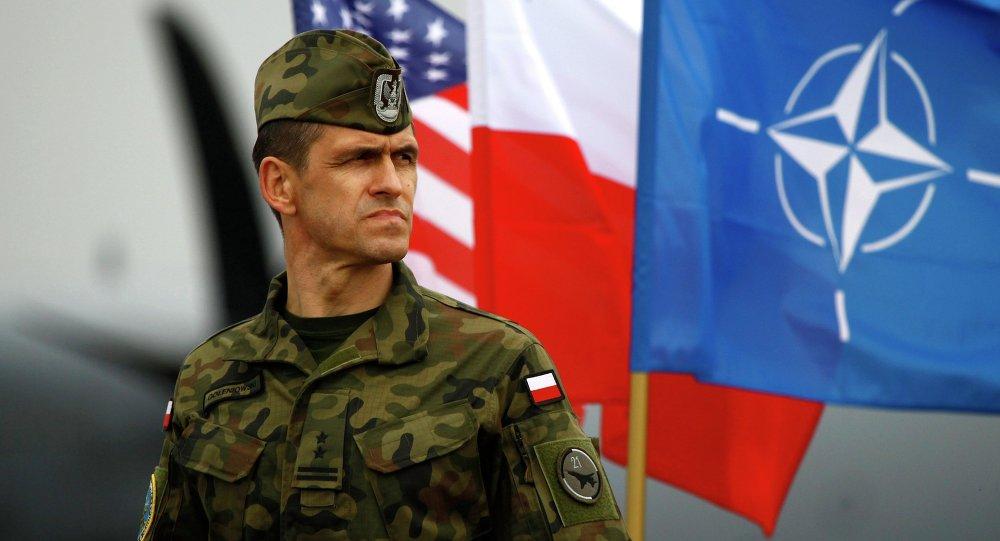 Un soldato polacco di fronte alle bandiere degli USA, della Polonia e della NATO