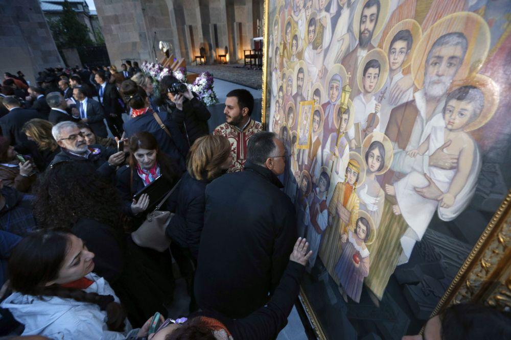 Armeni che baciano un'icona delle vittime canonizzate del massacro di Echmiadzin in una chiesa vicino a Erevan