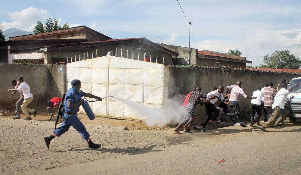 Un poliziotto del Burundi spara spray urticante contro dei manifestanti.