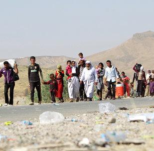 Profughi Yazidi varcano il confine iracheno-siriano nell'agosto del 2014