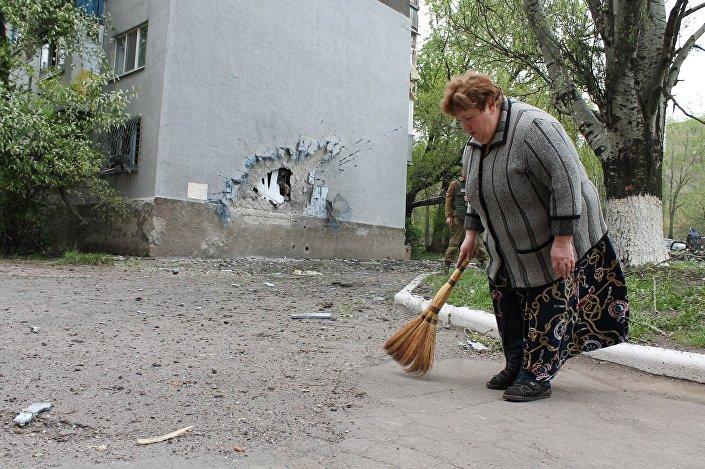 Una donna pulisce la strada davanti al suo palazzo bombardato dall'esercito ucraino.