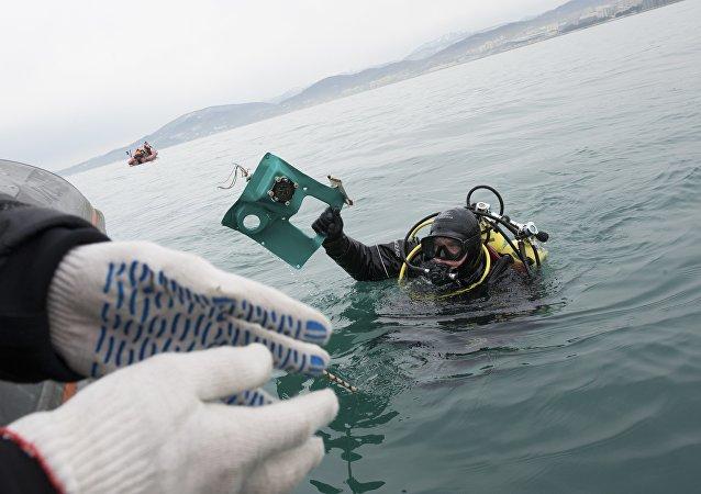 Soccorritori cercano frammenti dell'aereo Tu-154 schiantato a Sochi nel Mar Nero.