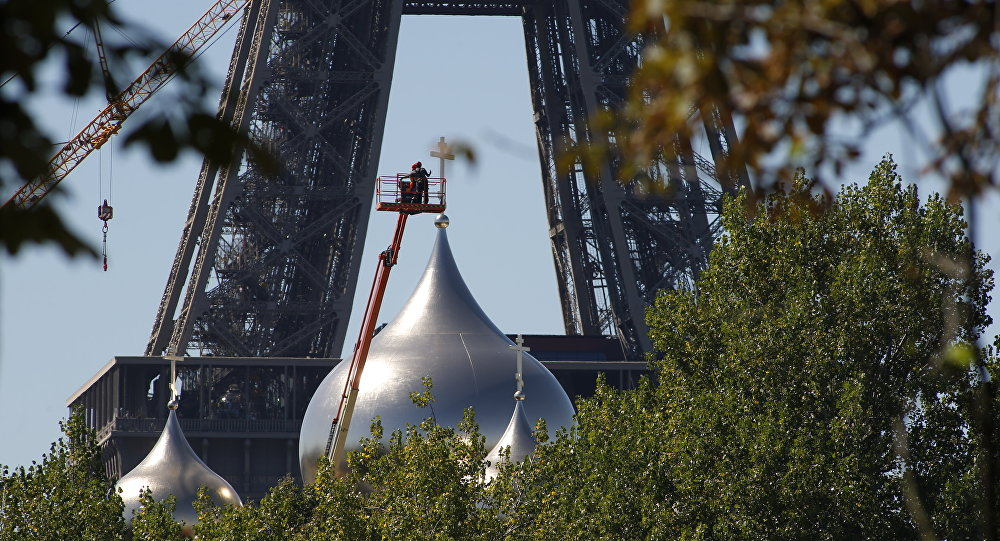 Men work on one of the five domes of the under construction Russian Orthodox Cathedral Sainte-Trinite at the Quai Branly, near the Eiffel Tower, on August 24, 2016 in Paris