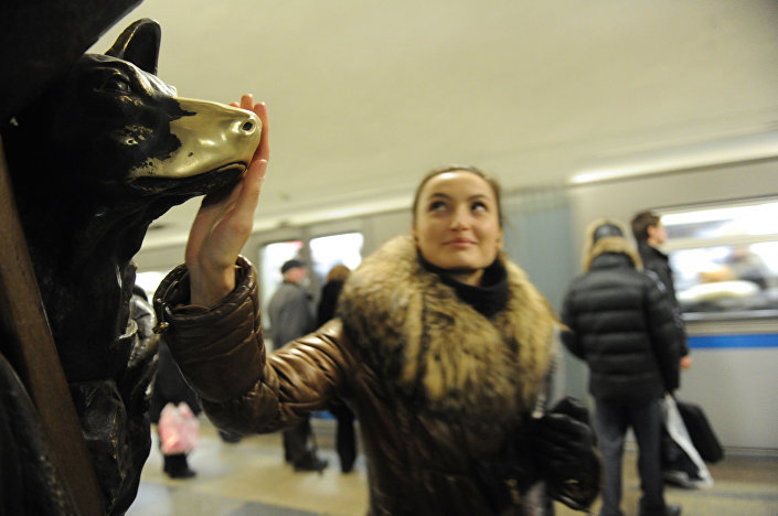 Una ragazza accarezza il cagnolino porta fortuna nella stazione Ploschad Revolyutsii della metropolitana di Mosca.
