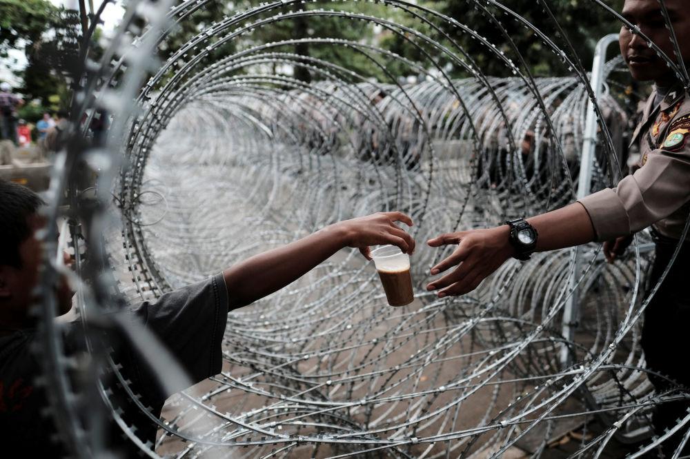 Un poliziotto indonesiano compra una bevanda tra un filo spinato vicino al tribunale di Giacarta dove si svolge il processo contro il governatore della città, Basuki Tjahaja Purnama.
