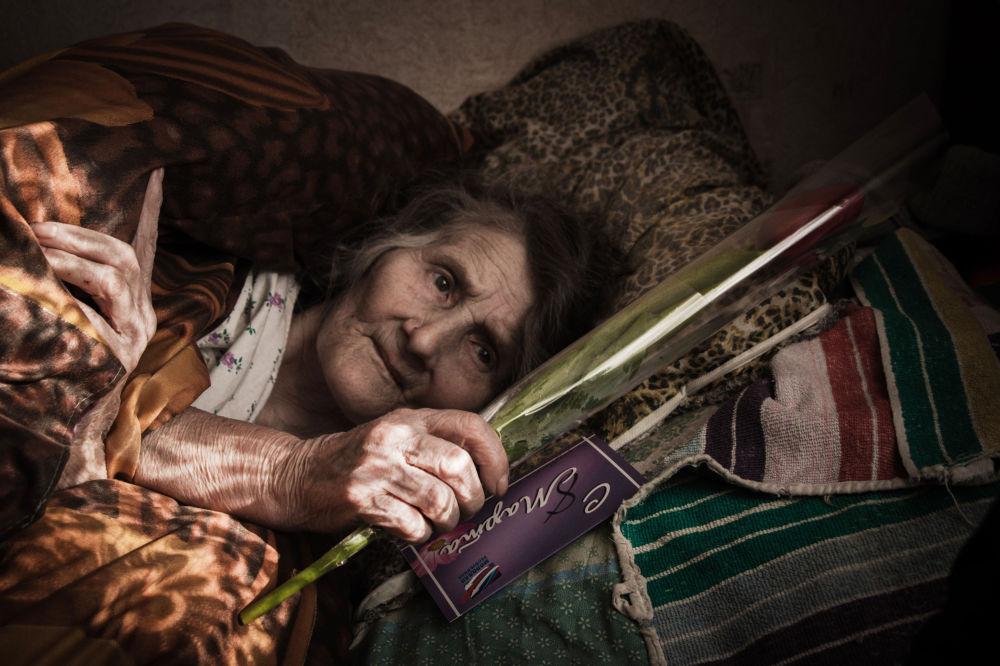 Una donna anziana celebra l'8 marzo, Giornata internazionale di donne, in un ospedale di Debaltsevo.