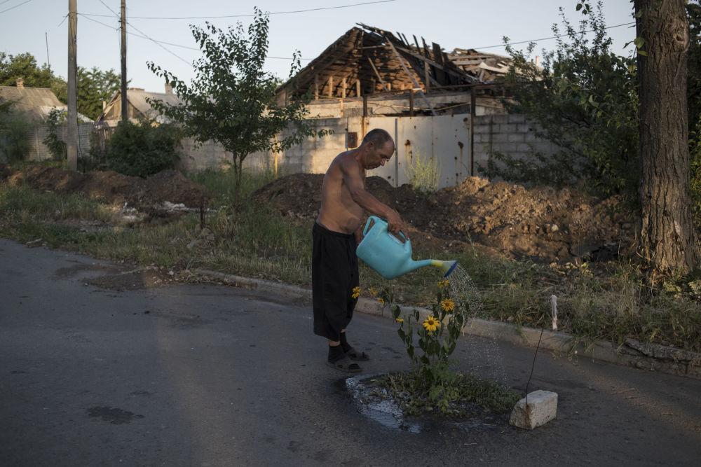 Un uomo annaffia i fiori in una delle vie della cittadina Veseloye nella regione di Donetsk.