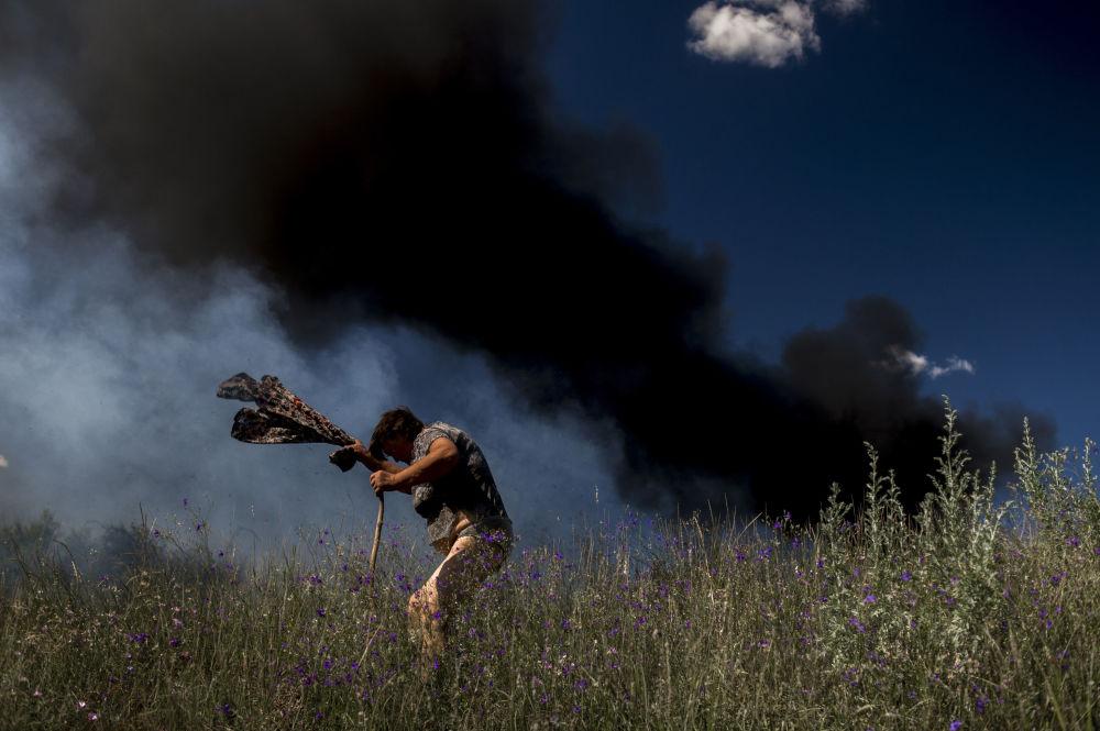 Una abitante locale vicino ad un auto infiammato da un proiettile durante i bombardamenti delle forze ucraina.