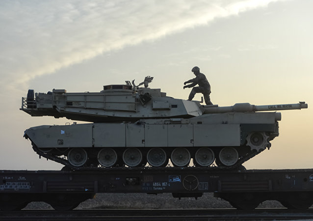 A serviceman of the Fighting Eagles 1st Battalion, 8th Infantry Regiment, walks on a tank that arrived via train to the US base in Mihail Kogalniceanu, eastern Romania, Tuesday, Feb. 14, 2017. Five hundred U.S. troops began to arrive in a Black Sea port in Romania with tanks and hardware to bolster defense in this East European NATO nation.