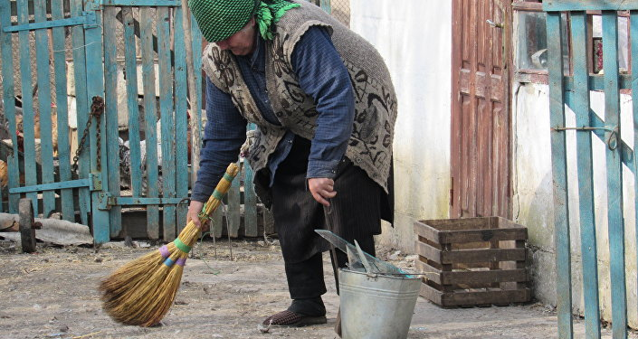 Un'anziana donna raccoglie frammenti di un vetro andato distrutto durante un bombardamento