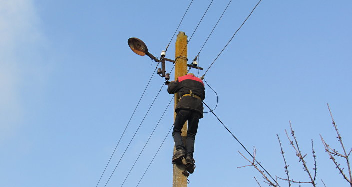 Kominternovo, un uomo ripara un traliccio dell'elettricità come se niente fosse